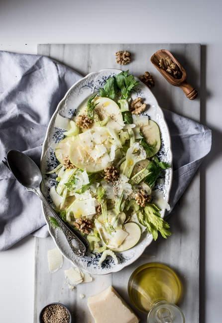 De arriba con deliciosas ensaladas hechas de manzanas, queso parmesano, nueces, apio y aceite sobre la mesa. - foto de stock