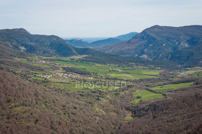 Scenic view of fields with small villages at foot of hills with trees — Stock Photo