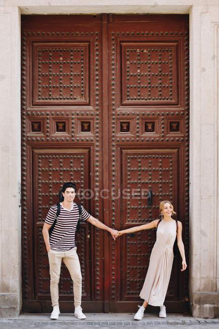 Joven pareja alegre y juguetona en ropa casual tomados de la mano frente a la hermosa puerta vieja - foto de stock