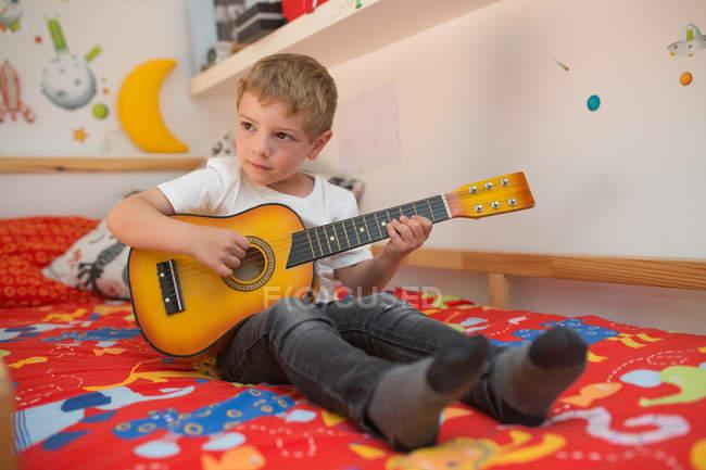 Kleiner blonder Junge spielt Spielzeuggitarre — Stockfoto