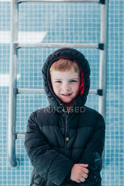 Garçon en vêtements chauds debout dans la piscine vide — Photo de stock