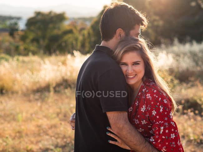 Hombre abrazando a la esposa sonriente en el fondo de la naturaleza - foto de stock