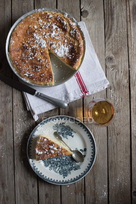 From above cottage cheese baked pudding served on vintage plate and towel against wooden table — Stock Photo