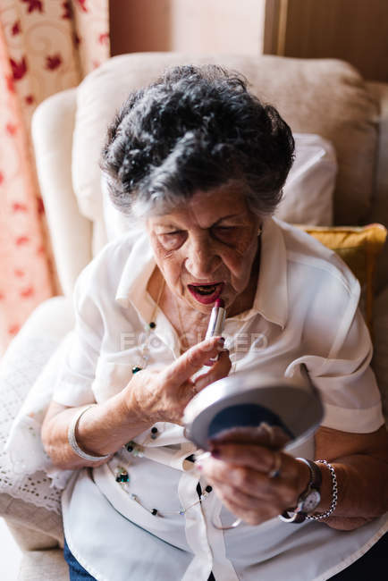 Senior woman applying lipstick while looking in mirror and sitting on armchair at home — Stock Photo