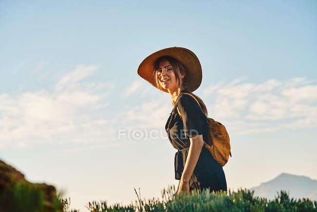 Turista fêmea que desgasta o chapéu de palha e a trouxa que andam na natureza e que olham a câmera — Fotografia de Stock