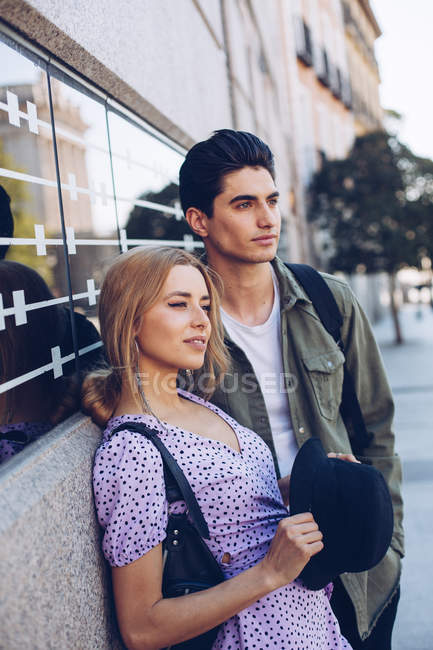 Joven pareja alegre en ropa casual de pie uno al lado del otro en la calle - foto de stock