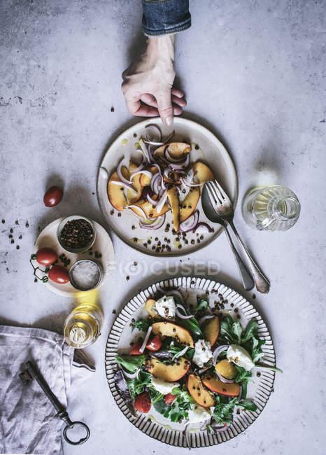 Von oben Hand des Menschen mit Sommersalat aus Früchten, Gemüse und Gewürzen — Stockfoto