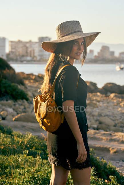Молоді жінки турист носіння соломи капелюх і рюкзака стояв біля пляжу — стокове фото