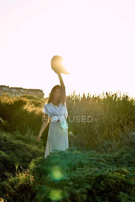 Young woman in white clothes looking at camera and holding hat in nature at sunset — Stock Photo