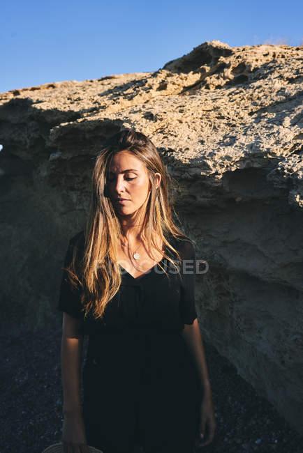 Junge nachdenkliche Frau blickt im Sonnenlicht mit Felsen im Hintergrund nach unten — Stockfoto