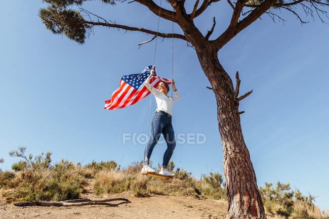 Юная девушка празднует 4 июля с американским флагом на качелях — стоковое фото