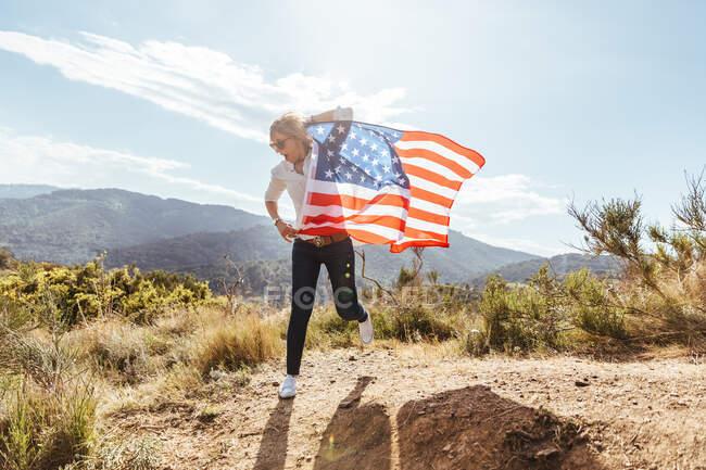 Giovane ragazza che festeggia il 4 luglio con una bandiera americana al tramonto — Foto stock