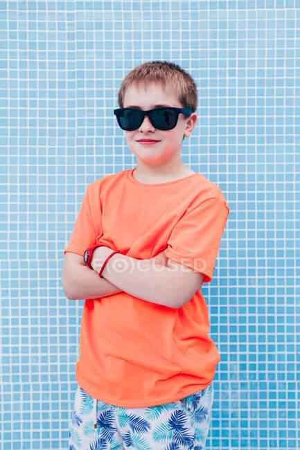 Счастливый мальчик в солнечных очках против плитки стены — стоковое фото