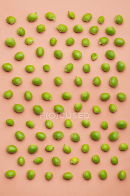 Set of peas scattered on salmon background — Stock Photo