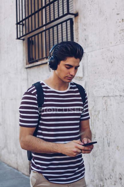 Attraente giovane uomo in abiti casual ascoltare musica durante la passeggiata in strada alla luce del giorno — Foto stock