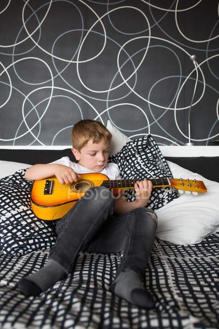 Jovem loira menino tocando guitarra brinquedo — Fotografia de Stock