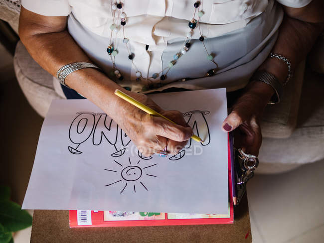 Cropped image of senior woman in white shirt and glasses drawing on paper with pencil, sitting on armchair at home — Stock Photo