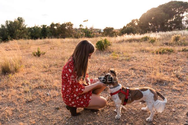 Молода жінка з довгим волоссям грати і даючи прихильність до милої собакою — стокове фото