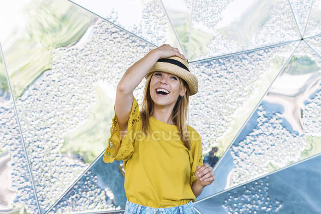 Young stylish cheerful woman posing in straw hat on metal background — Stock Photo