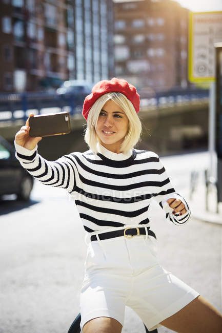 Young smiling pretty woman in French red cap, striped blouse and white shorts taking photo on urban background — Stock Photo