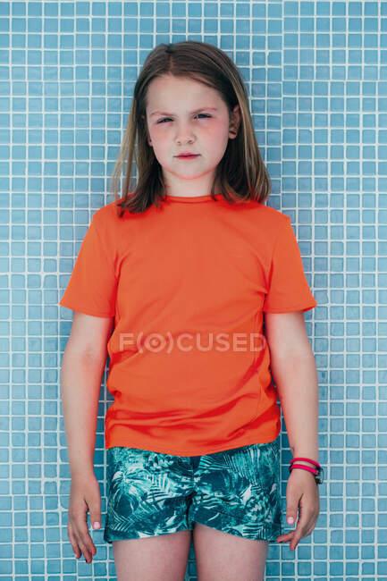 Retrato de una niña seria con una camiseta naranja brillante parada junto a la pared de la piscina y mirando a la cámara - foto de stock