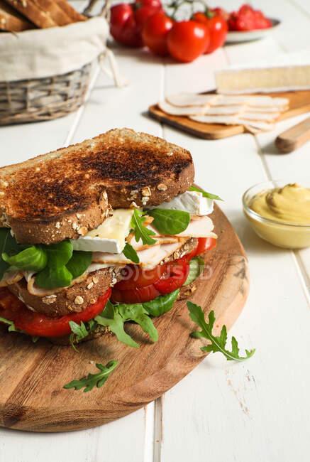Verduras frescas y queso en medio de rebanadas de pan frito con jamón sobre una mesa blanca - foto de stock