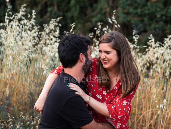 Людина обіймає усміхнену дружину вагітну, сидячи на колінах на фоні мальовничого зеленого парку в сонячний день — стокове фото