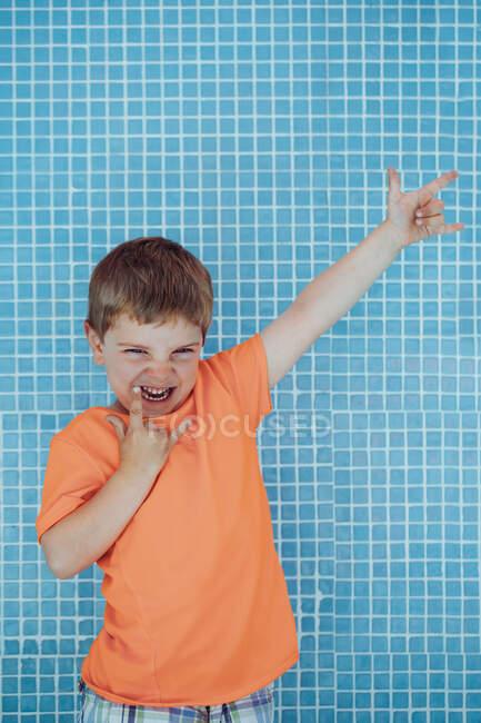 Радостный мальчик в ярко-оранжевой футболке с жестом скалы на фоне кафельной стены бассейна — стоковое фото