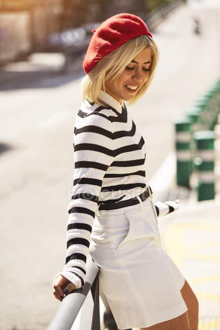 Молодая блондинка в полосатой черно-белой рубашке и красной французской кепке опирается на перила на размытом городском фоне — стоковое фото