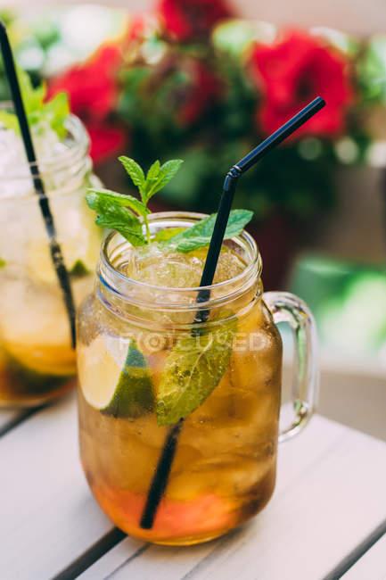Cocktail di mojito preparato con lime, menta, rum, soda e ghiaccio in vasetto di muratore in tavola all'aperto — Foto stock