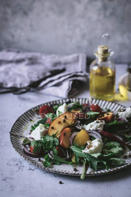 Prato com salada gourmet feita de pêssegos, cebola vermelha, queijo e pimenta preta na mesa — Fotografia de Stock