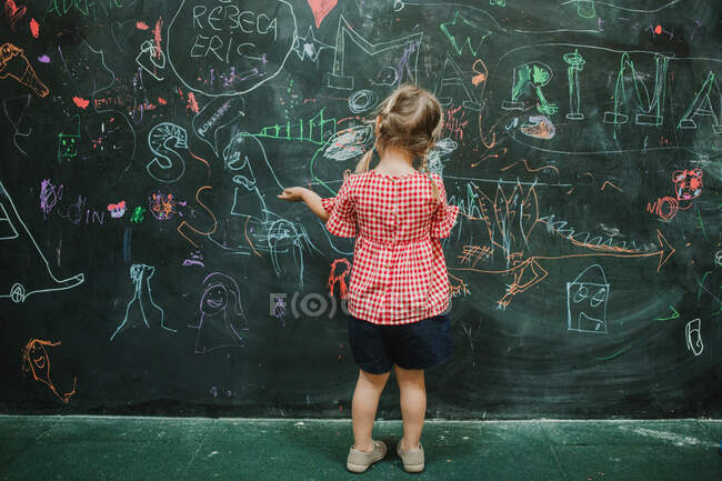 Back view of unrecognizable adorable child drawing at school during class in a writing green board — Stock Photo