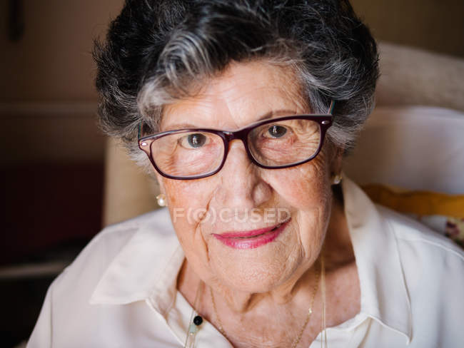 Smiling senior woman in glasses with pink lips looking at camera in apartment — Stock Photo