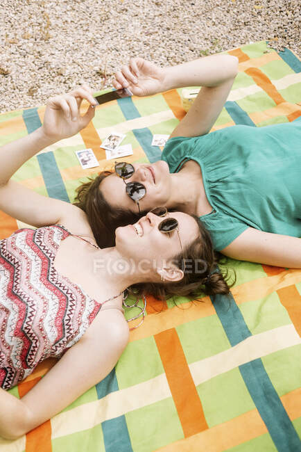 From above young attractive women in bright clothes and black sunglasses lying on colorful blanket and looking at instant photos — Stock Photo
