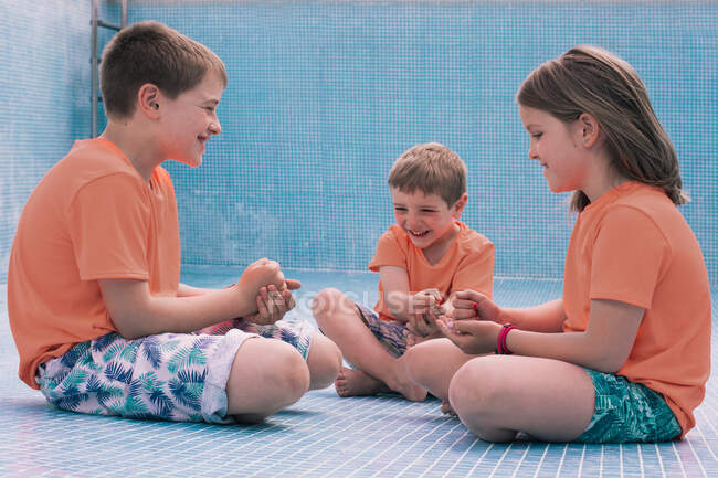 Children playing rock-paper-scissors in empty pool — Stock Photo