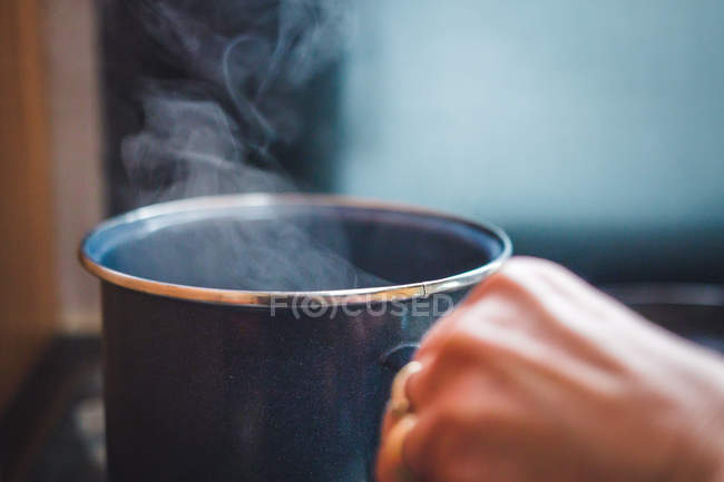 Closeup hand of anonymous person holding metal mug with steamy hot beverage — Stock Photo