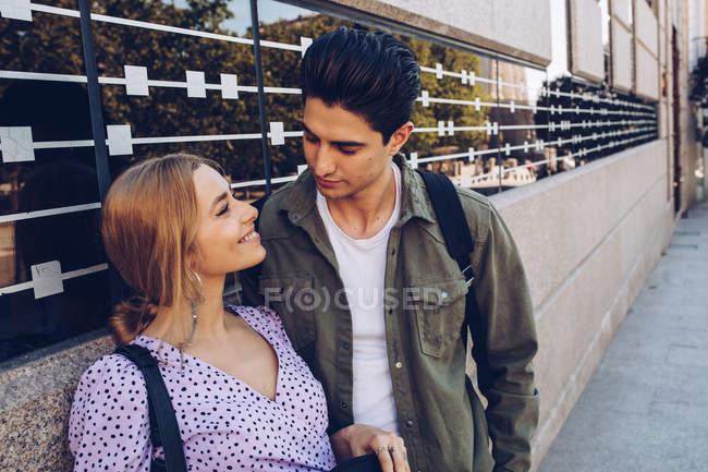 Joven pareja alegre en ropa casual vinculación durante citas al aire libre - foto de stock