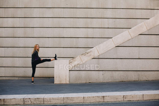 Young blonde woman stretching in a staircase after a running session — Stock Photo