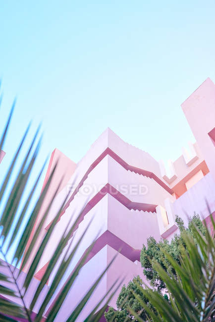 Pink building of complex geometric shape under blue sky — Stock Photo