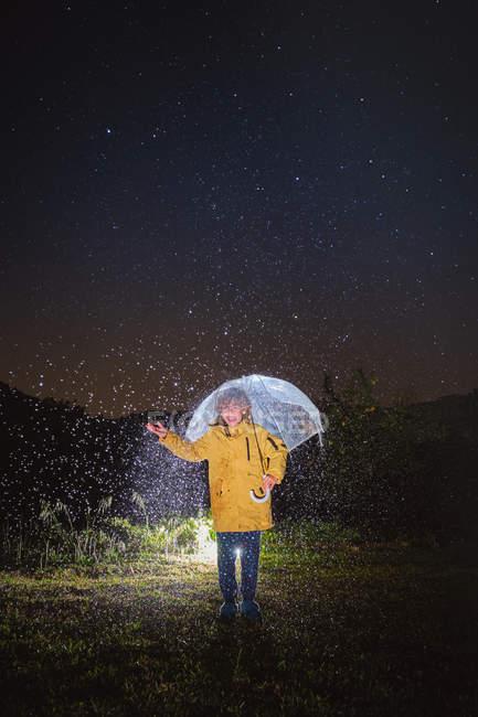 Ребенок в желтой куртке стоит под белым зонтиком, звезды в темноте ночи — стоковое фото