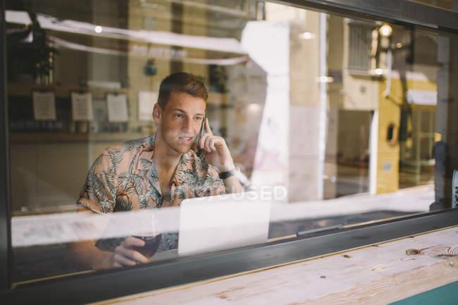 Focalizzato giovane uomo parlando su smartphone durante l'utilizzo del computer portatile a tavola durante le finestre in caffetteria — Foto stock