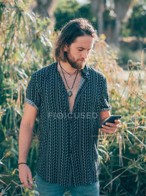 Jeune hipster barbu en chemise textant sur téléphone portable dans la jungle tropicale — Photo de stock