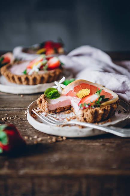 Dall'alto porzioni di deliziose torte di fragole e agrumi servite su tavolo di legno decorato — Foto stock