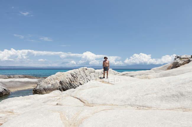 Abbronzato uomo maturo in piedi sulla spiaggia rocciosa bianca con cielo blu e nuvole, Calcidica, Grecia — Foto stock