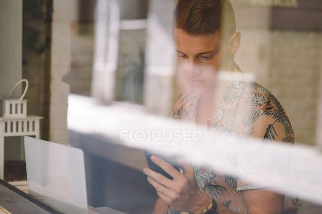 Focalizzato giovane uomo utilizzando smartphone durante l'utilizzo del computer portatile a tavola durante le finestre in caffetteria — Foto stock