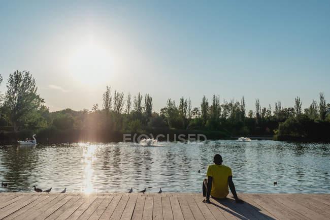 Задній вид людини, що сидить на дерев'яній пристані, спираючись на руки для відпочинку в сонячному денний — стокове фото