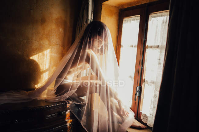 Naked sensual woman covered with transparent white cloth sitting near window in sunlight — Stock Photo