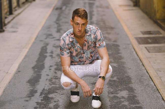 Красивый мужчина в гавайской рубашке, сидя на асфальте на улице и глядя в сторону — стоковое фото