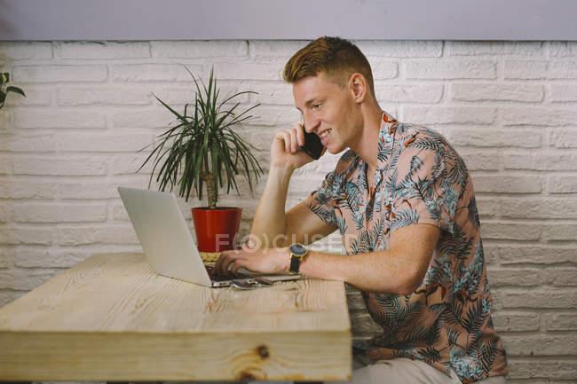Uomo concentrato che parla sullo smartphone mentre utilizza il computer portatile a tavola in caffetteria — Foto stock