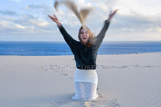 Cheerful playful woman throwing pile of sand at camera while sitting on empty coastline in Tarifa, Spain — Stock Photo
